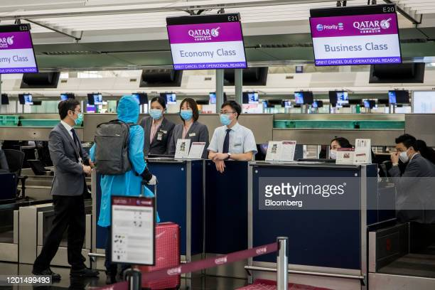 Traveler speaks with employees wearing face masks at the Qatar Airways check-in counter at Hong Kong International Airport in Hong Kong, China, on...
