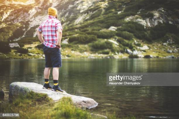 traveler standing at the lake in mountains - pirin national park stock pictures, royalty-free photos & images