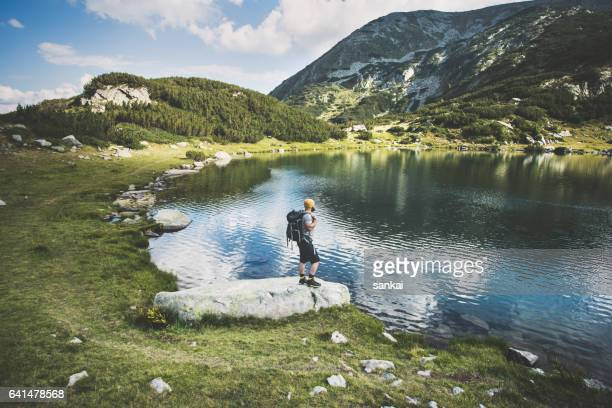 traveler standing at the lake in mountains - pirin mountains stock pictures, royalty-free photos & images