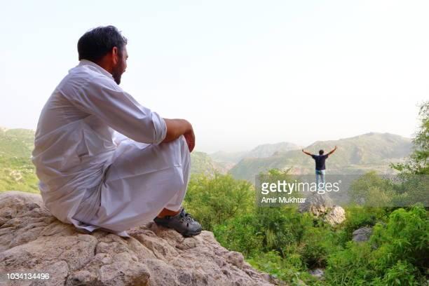 Traveler standing on rock, watching and enjoying nature scene