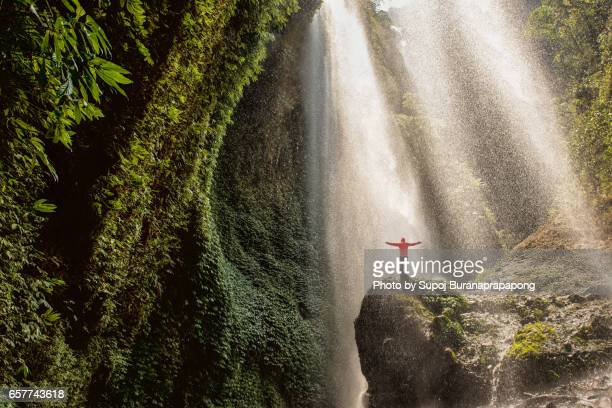 traveler standing on the rock in the tropical rainforest at madakaripura waterfall , east java , indonesia - java indonesia fotografías e imágenes de stock