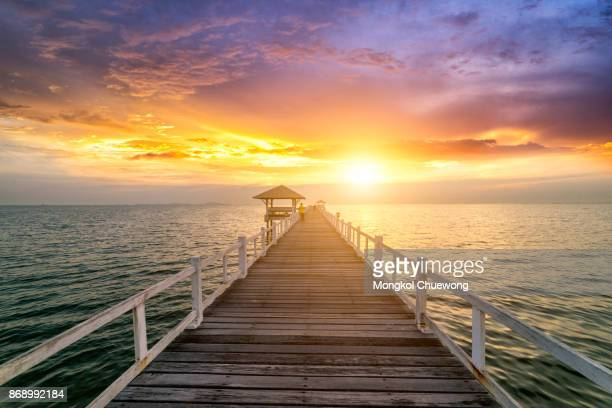 Traveler standing on wooden bridge in the sea at sunset scence