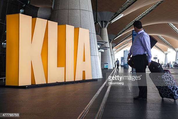 A traveler stands beside Kuala Lumpur International Airport signage as he arrives at the airport's departures hall in Sepang Malaysia on Tuesday...