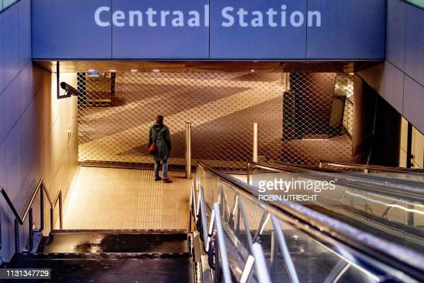 A traveler stands in front of the closed Amsterdam Central station on March 18 2019 on the national action day for a better pension during which no...