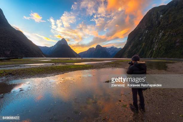 A traveler take a photograph at Milford sound