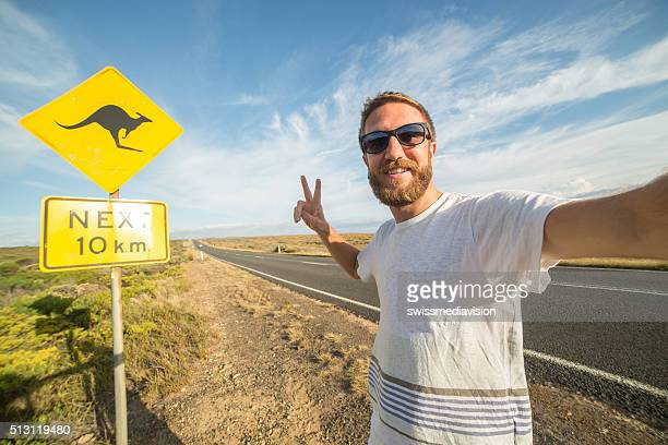 Traveler takes selfie portrait standing next to kangaroo warning sign