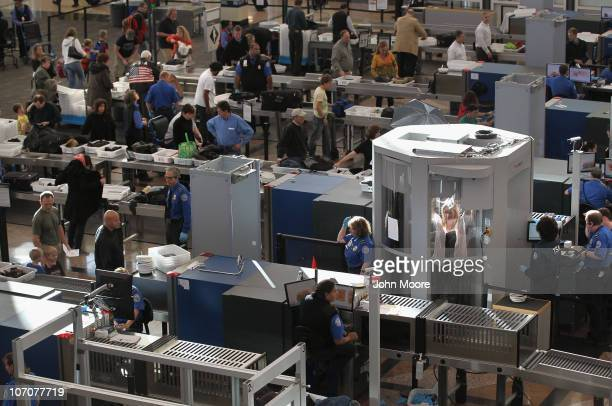 A traveler undergoes a full body scan performed by Transportation Security Administration agents as she and others pass through the security...