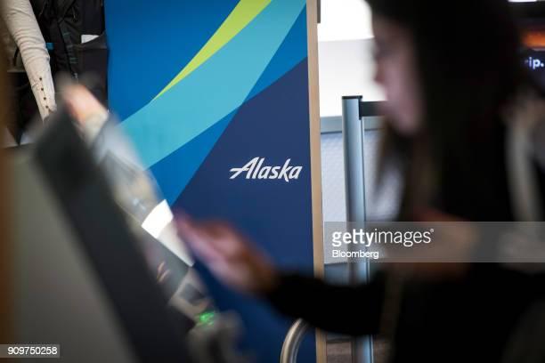 A traveler uses an Alaska Air Group Inc self checkin kiosk at the San Francisco International Airport in San Francisco California US on Friday Jan 19...