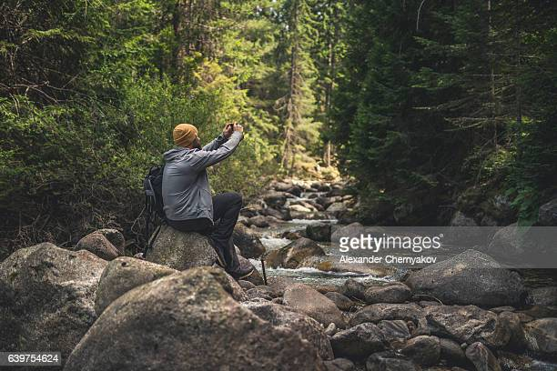 Traveler uses smartphone at the stream in forest
