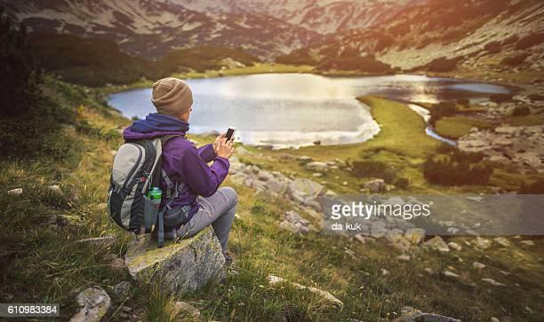 Traveler using a smart phone in mountains sitting near lake