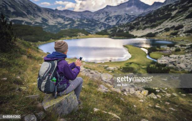 traveler using a smart phone in mountains sitting near lake - pirin national park stock pictures, royalty-free photos & images