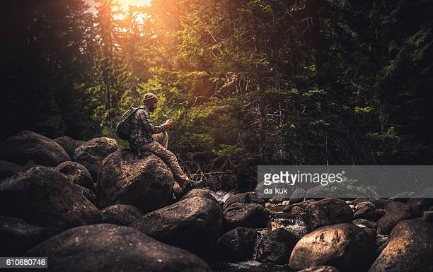 Traveler using a smart phone in the forest