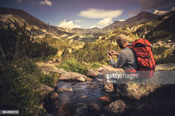 traveler using a smartphone in the mountains - pirin national park stock pictures, royalty-free photos & images