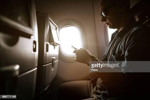 Traveler Using Phone In Airplane