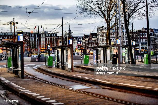 A traveler waits at the Amsterdam Central station on March 18 2019 on the national action day for a better pension during which no trains trams buses...