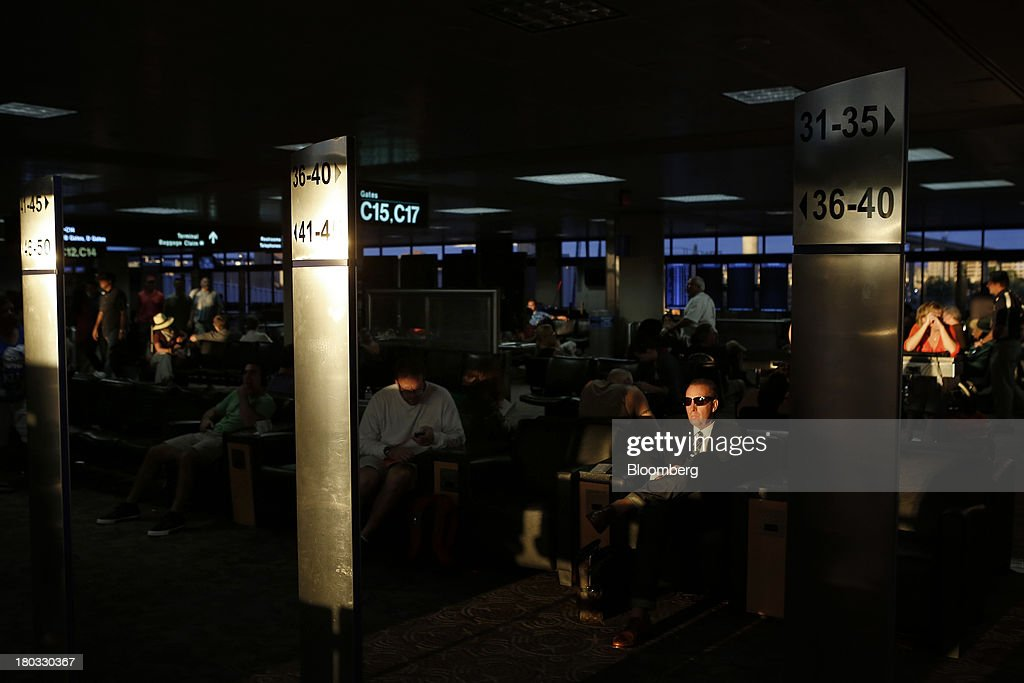 A traveler waits for a flight at Phoenix Sky Harbor International Airport (PHX) in Phoenix, Arizona, U.S., on Sunday, Sept. 8, 2013. Yields on benchmark securities climbed to almost two-year highs as consumers spent more on travel and tourism while manufacturing expanded modestly from early July through late August, according to the Federal Reserves Beige Book. Photographer: Patrick T. Fallon/Bloomberg via Getty Images