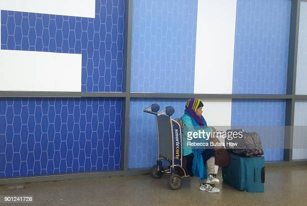 A traveler waits in terminal five at John F Kennedy International Airport on January 4 2018 in the Queens borough of New York City A winter storm is...