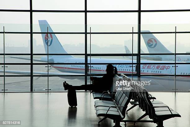 A traveler waits on a bench in front of a window overlooking parked China Eastern passenger jets at the Shanghai Hongqio Airport in Shanghai China on...