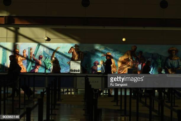 Traveler walk past art work at Denver International Airport on January 3 2018 in Denver Colorado