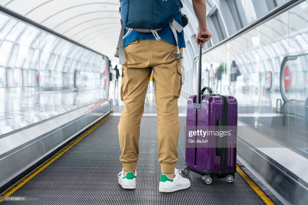 A Traveler walking on moving walkway in the airport : Stock Photo