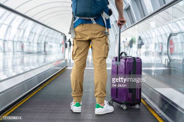 a traveler walking on moving walkway in the airport - emigration and immigration stock pictures, royalty-free photos & images