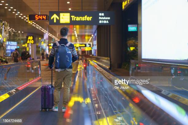 a traveler walking on moving walkway in the airport - travolator stock pictures, royalty-free photos & images