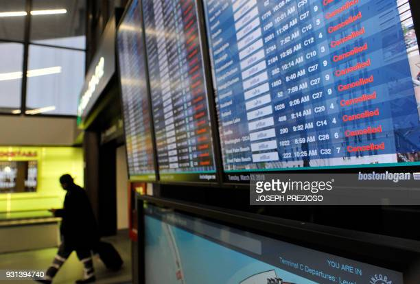 A traveler walks by a board showing all flights canceled at Boston Logan Airport during a March noreaster on March 13 2018 / AFP PHOTO / Joseph...
