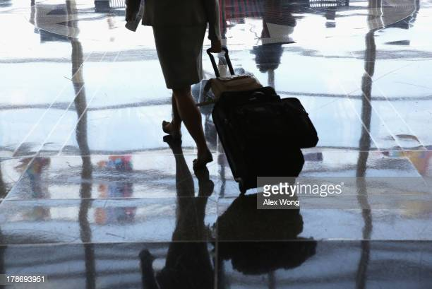 A traveler walks in a terminal of the Ronald Reagan National Airport August 30 2013 in Arlington VA According to an AAA forecast about 341 million...