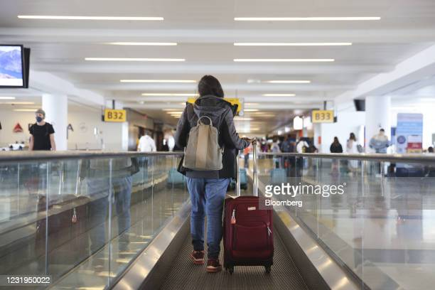 Traveler walks on a moving walkway in Terminal 4 at John F. Kennedy International Airport in New York, U.S., on Friday, March 26, 2021. The TSA...