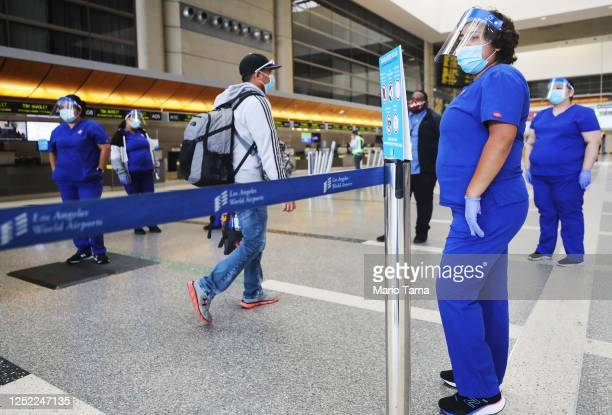 A traveler walks past screeners testing a system of thermal imaging cameras which check body temperatures at Los Angeles International Airport amid...