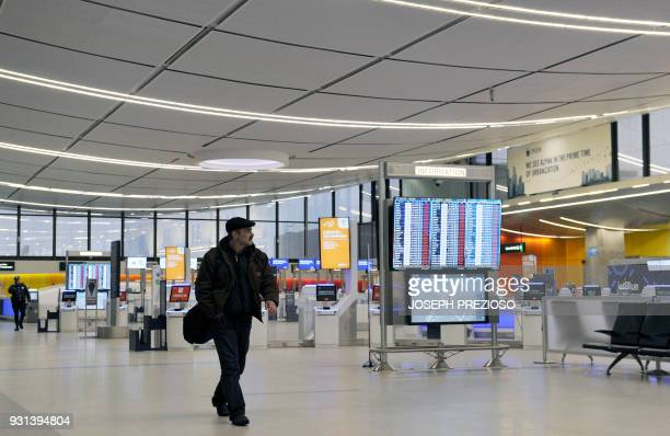 A traveler walks though an empty Boston Logan Airport during a March noreaster on March 13 2018 / AFP PHOTO / Joseph PREZIOSO / The erroneous...