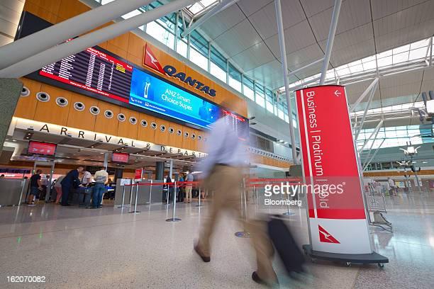 A traveler walks through the Qantas Airways Ltd domestic terminal at Sydney Airport in Sydney Australia on Tuesday Feb 19 2013 Qantas Airways is...