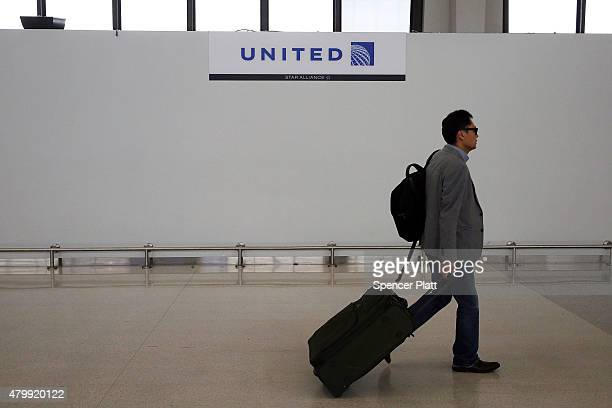 A traveler walks through the United Airlines terminal at Newark Liberty Airport on July 8 2015 in Newark New Jersey A computer system glitch caused...