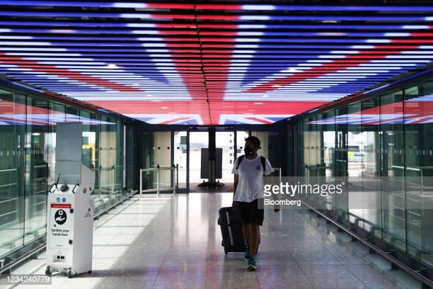 Traveler walks underneath a British Union Flag at Terminal 5 in London Heathrow Airport Ltd. In London, U.K., on Tuesday, July 27, 2021....