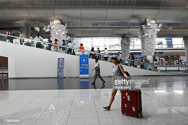 A traveler walks with her baggage as people ride an escalator at Incheon International Airport in Incheon South Korea on Thursday Aug 8 2013 South...