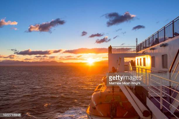 a traveler watches the sun set over the horizon as he crosses the cook straight in new zealand. - beauty in nature stock pictures, royalty-free photos & images