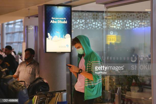 Traveler wearing a face mask to protect from them the novel coronavirus while travelling through Abu Dhabi International Airport in Abu Dhabi United...