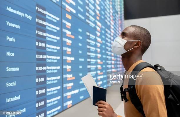 reisender trägt eine gesichtsmaske am flughafen und schaut sich den flugplan an - passagier stock-fotos und bilder