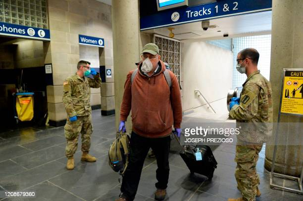 Traveler wearing a mask and gloves walks past US Army National Guard soldiers at the Amtrack Station in Providence, Rhode Island on March 30 during...