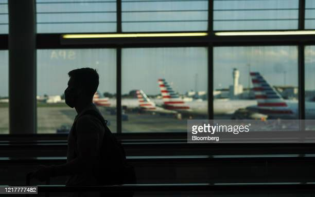 Traveler wearing a protective mask passes in front of American Airlines airplanes at the Charlotte Douglas International Airport in Charlotte, North...