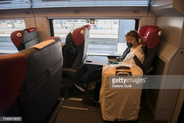 A traveler wearing a protective mask sits inside a Italo Train before departing at the Porta Nuova railway station on June 03 2020 in Turin Italy...