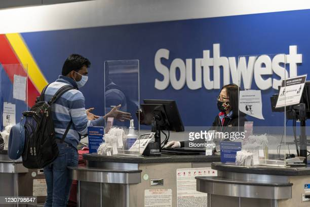 Traveler wearing a protective mask speaks with an attendant at the Southwest Airlines check-in area at Oakland International Airport in Oakland,...