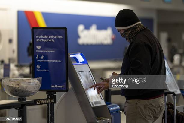 Traveler wearing a protective mask uses an automated check-in kiosk at the Southwest Airlines check-in area at Oakland International Airport in...