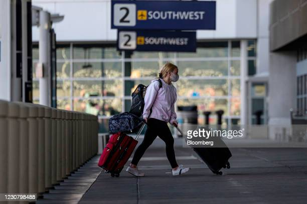 Traveler wearing a protective mask walks to the Southwest Airlines check-in area at Oakland International Airport in Oakland, California, U.S., on...