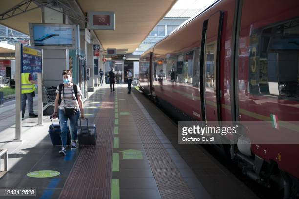 A traveler wearing a protective mask walks with luggage to board the interregional train at the Porta Nuova railway station on June 03 2020 in Turin...
