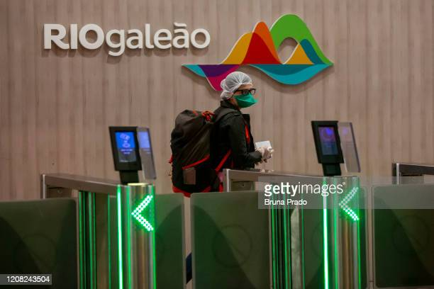 A traveler wearing protective face mask walks at the Tom Jobim International Airport on March 25 2020 in Rio de Janeiro Brazil The federal government...