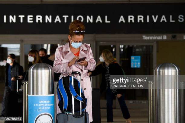 Traveler wears a face mask while checking their phone on the arrivals level outside the Tom Bradley International Terminal at Los Angeles...