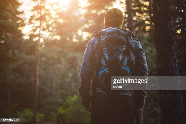 Traveler with a backpack in the the forest