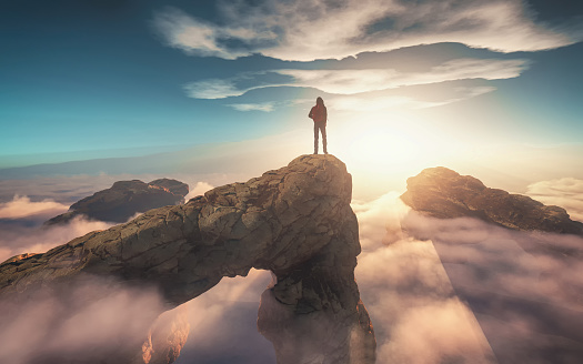 Traveler with a backpack standing on a mountain peak above clouds. 3d render illustration 1189860501