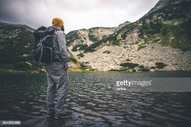 traveler with a backpack stands alone at the lake in mountains. - pirin national park stock pictures, royalty-free photos & images